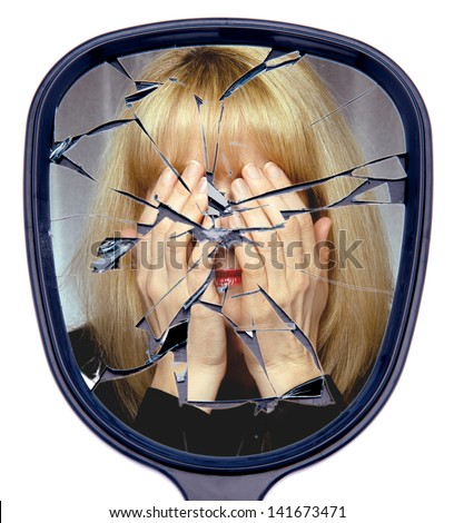 A woman covers her face reflected in a  broken mirror or the shattered life concept - stock photo