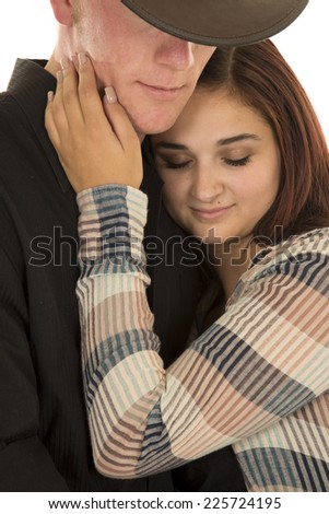 A woman cuddling up close to her cowboy with her eyes closed. - stock photo