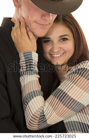 A woman cuddling up to her cowboy with a smile on her face. - stock photo