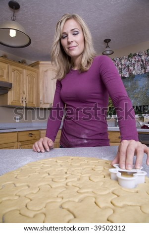 A woman cutting lots of shapes out of the dough.