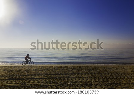 A woman cycles along a mediterranean beach on a sunny day./ Cycling along a beach - stock photo
