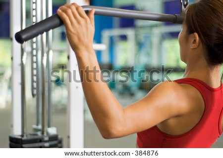 A woman demonstrates a lat pulldown exercise in a gym - stock photo