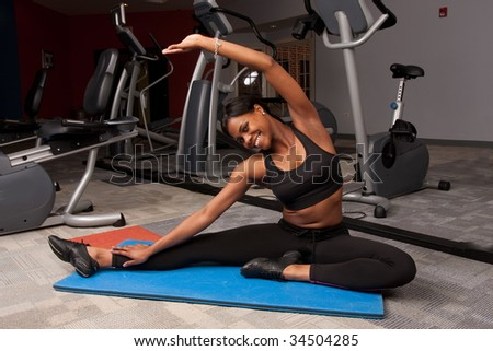 a woman does yoga in a gym - stock photo