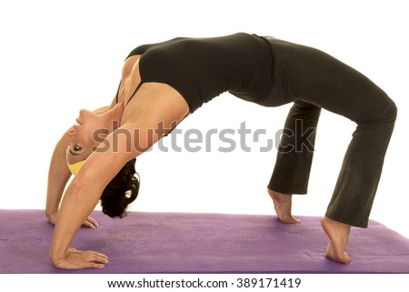 a woman doing a back bend stretching her body out. - stock photo