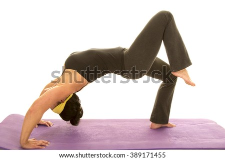 a woman doing a back bend stretching out her body, while doing fitness. - stock photo
