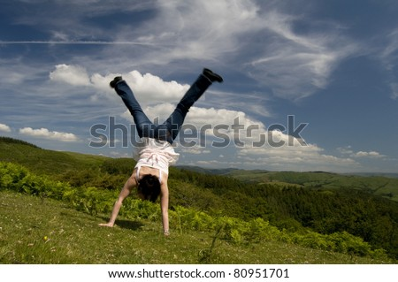 a woman doing a cartwheel on top of a hill - stock photo