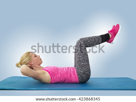 A woman doing a crunch on her fitness mat. - stock photo