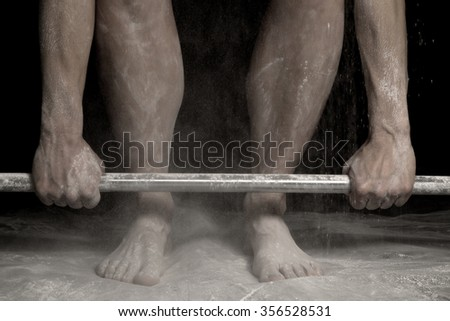 A woman doing a dead lift close up with powder on her legs and arms. - stock photo