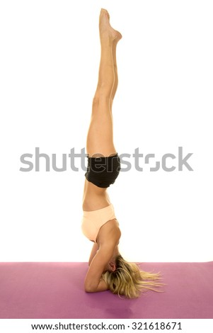 a woman doing a head stand, showing off her balance on her fitness mat. - stock photo