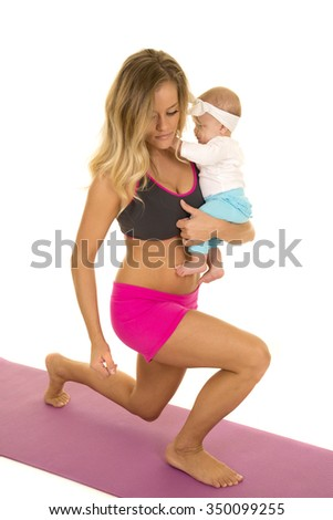 A woman doing a lunge with her baby on her hip.