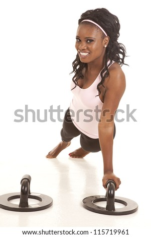 A woman doing a one arm push up with a smile on her face. - stock photo