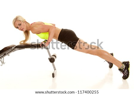 A woman doing a push up on a bench.