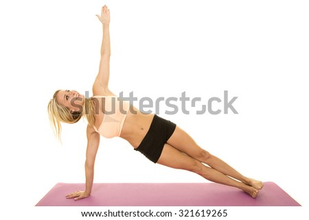a woman doing a side plank on her fitness mat. - stock photo