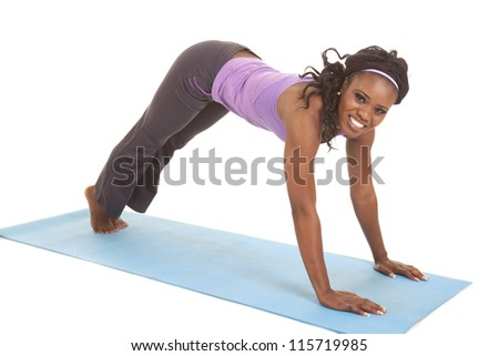 A woman doing a upward dog pose stretching her arms and legs with a smile on her face. - stock photo