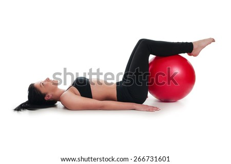 A woman doing exercise for stomach muscle with fitness ball - stock photo