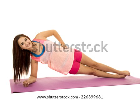A woman doing her side plank on her fitness mat. - stock photo