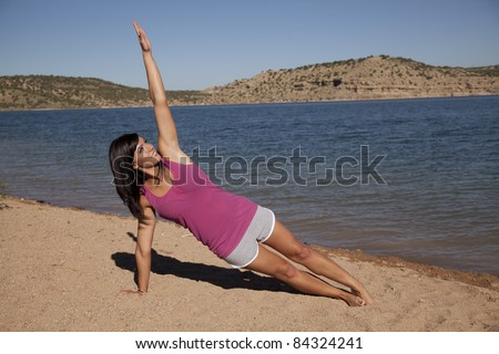 A woman doing her yoga stretch on the beach with a smile on her face. - stock photo