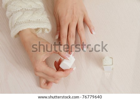 A woman doing manicure, focus on her hands