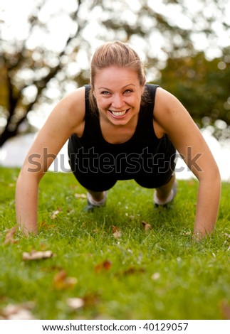 A woman doing push-ups in the park - stock photo