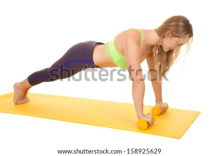 a woman doing push ups on her fitness mat with a smile. - stock photo