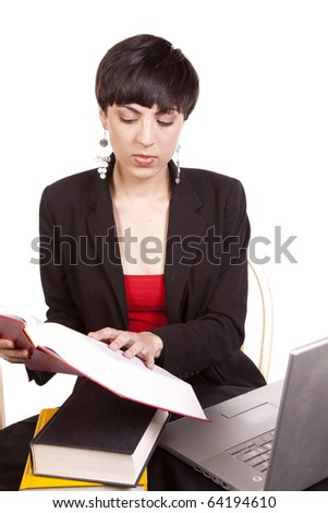 A woman doing work and looking in her books for some answers. - stock photo