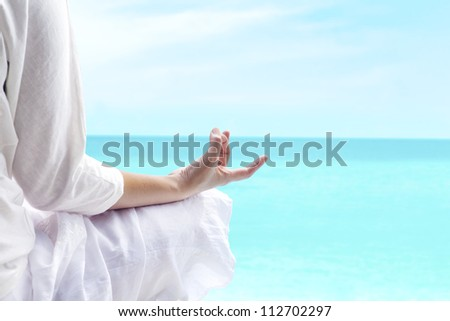 A woman doing yoga exercise with ocean view