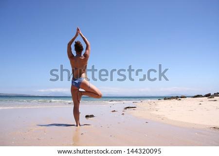 A woman doing yoga on the beach - stock photo