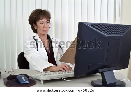A woman dressed as a doctor working on a computer. - stock photo