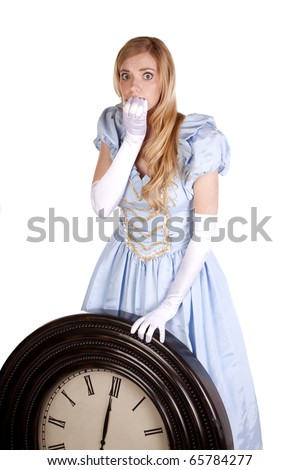 A woman dressed in a cinderella dress holding up a big clock scared to know that it is midnight. - stock photo