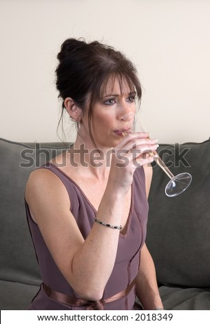 A woman, dressed up for an evening party, staring off into space as she drinks champagne alone.