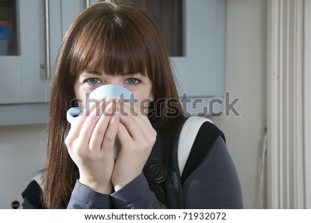 A woman drinking a hot drink at home. - stock photo