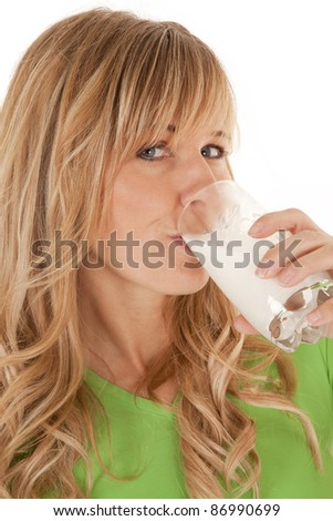 A woman drinking her milk from a glass enjoying every sip. - stock photo