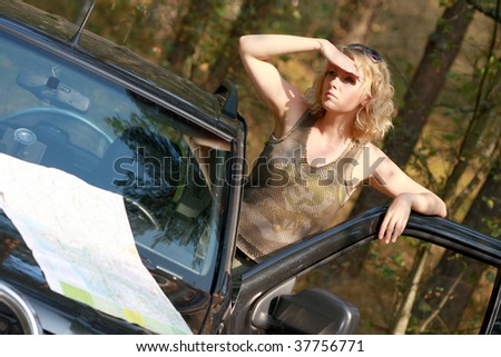 A woman driver reading a road map - stock photo