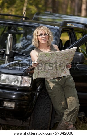 A woman driver reading a road map