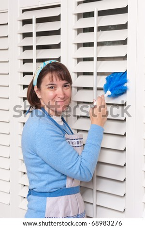 A woman dusting her dirty window shutters.