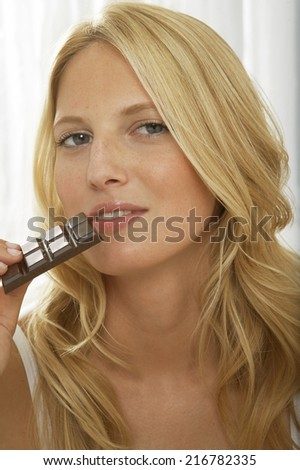 A woman eating chocolate. - stock photo