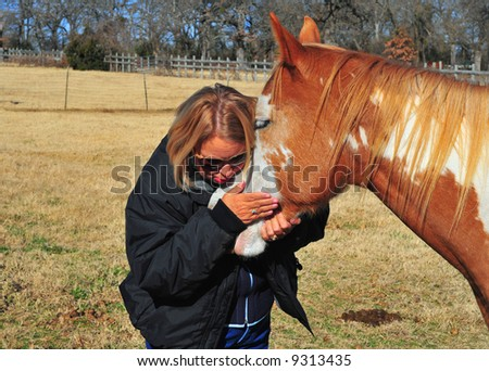 A woman embraces her horse affectionately - stock photo