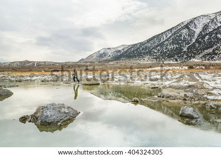 A woman enjoy her time at Mono Lake, Eastern Sierra, California in winter with full of snow on her way.  The picture is perfect for projects, travel agencies, hotels, hostels, and motels - stock photo