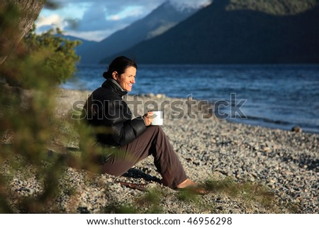 A woman enjoying her first cup of coffee. - stock photo