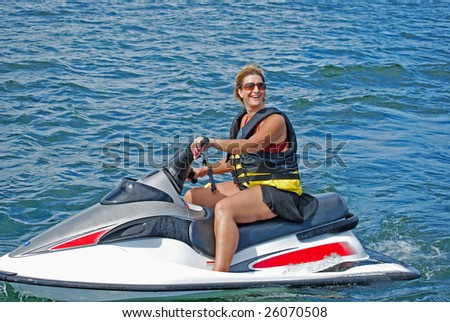 a woman enjoys a ride on a personal water craft on a beautiful summer day - stock photo
