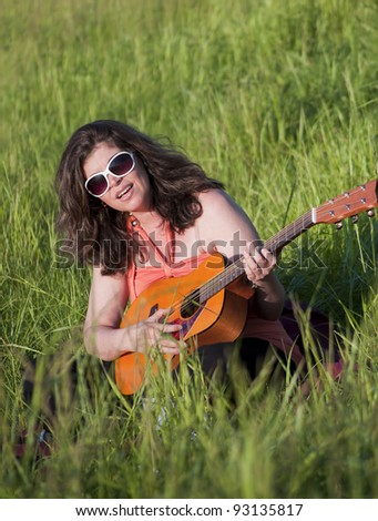 A woman enjoys time outdoors playing her guitar - stock photo