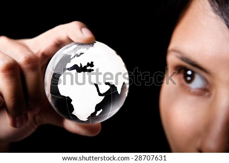 A woman examining a glass globe which showing Africa and Europe continent - stock photo