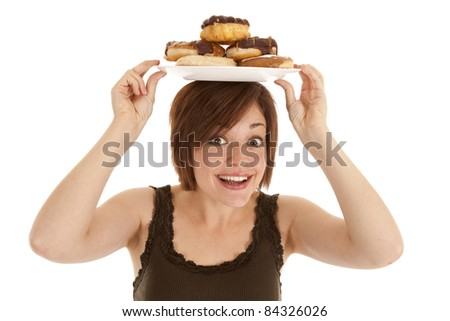 A woman excited about the pile of doughnuts she has on her head. - stock photo