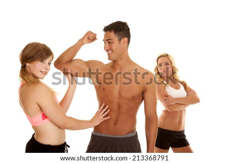A woman feeling his mans muscles while the women in the background is jealous. - stock photo