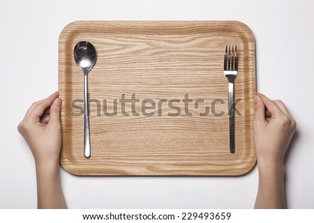 A woman(female) two hands hold a empty(blank) wooden tray with iron spoon and chopsticks isolated white, top view, studio. - stock photo