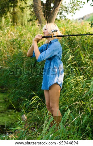 a woman fishes in the river fishing-rod. on a background a river reed