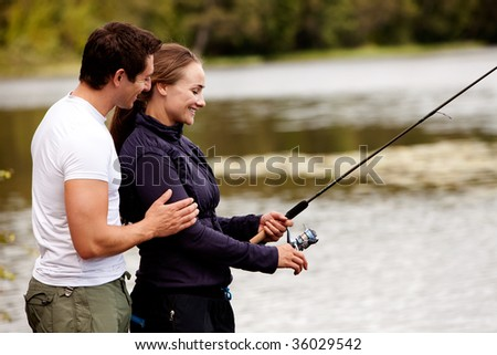 A woman fishing on a interior forest lake - stock photo