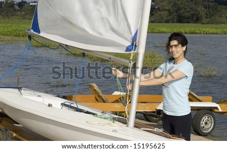 A woman fixes the sail on her boat by pulling the ropes.  She is looking at the camera and smiling.  Horizontally framed shot. - stock photo