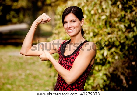 A woman flexing her biscep and making it larger - stock photo
