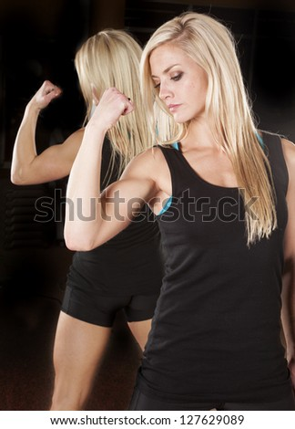 A woman flexing her muscles looking down.